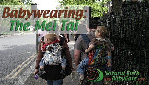 family carrying two babies in mei tai carriers