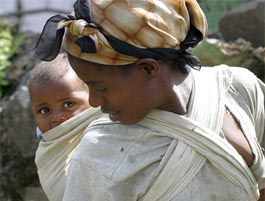 mother with her baby in a wrap baby carrier