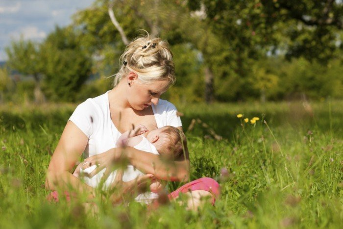 Mother breastfeeds her newborn outside